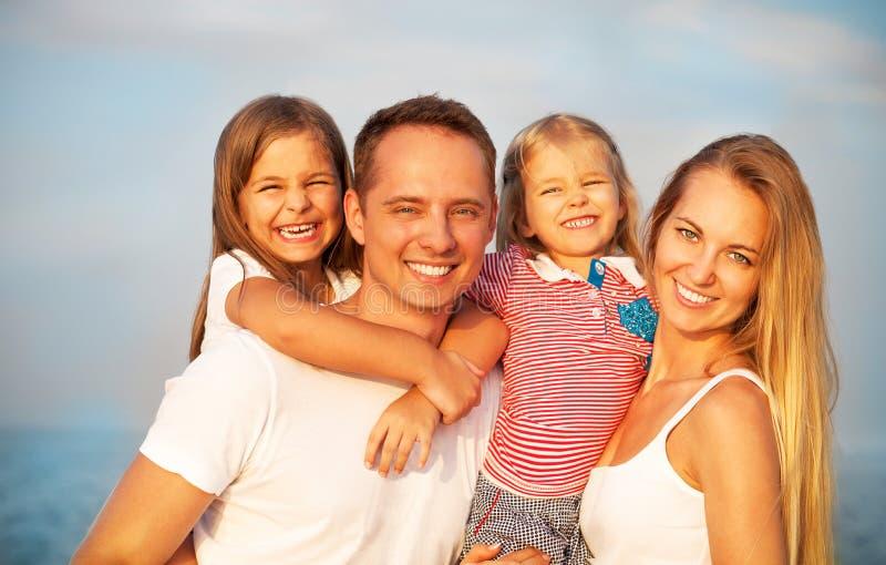 Gelukkige jonge familie met twee kinderen in openlucht zomer stock fotografie