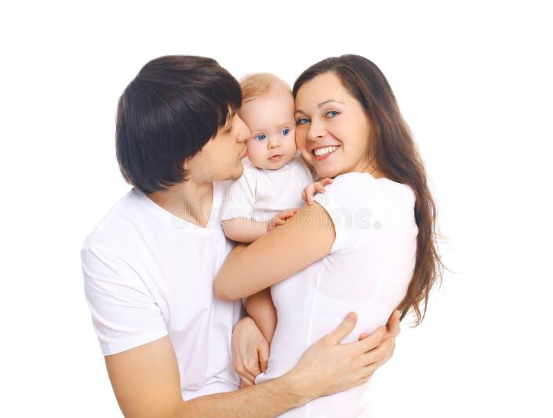 Gelukkige jonge familie, moeder en vader kussende baby op een wit stock foto