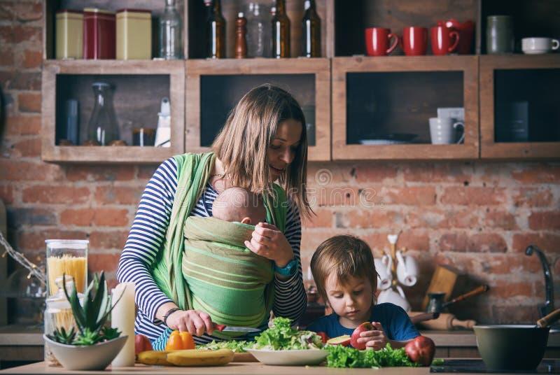 Gelukkige jonge familie, mooie moeder met twee kinderen, aanbiddelijke peuterjongen en baby in slinger het koken samen in een zon stock foto's