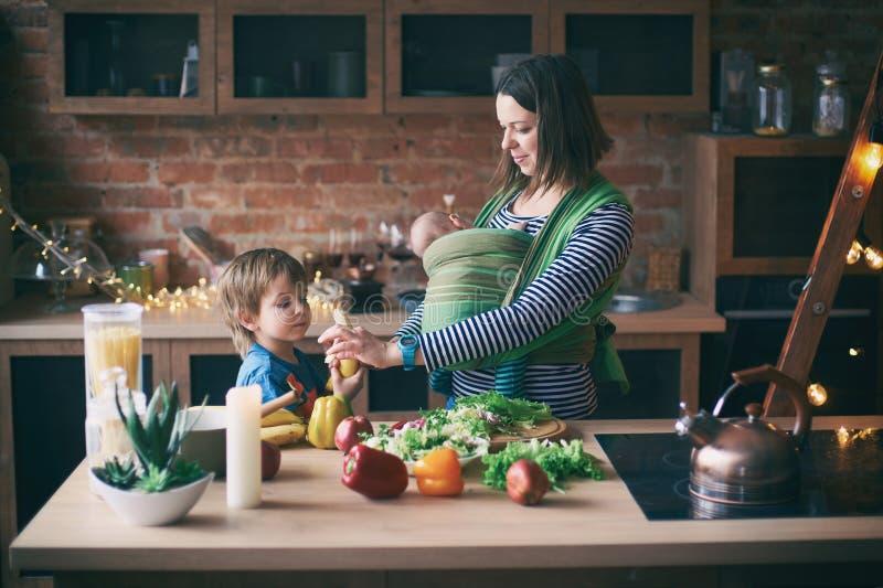 Gelukkige jonge familie, mooie moeder met twee kinderen, aanbiddelijke peuterjongen en baby in slinger het koken samen in een zon royalty-vrije stock foto's