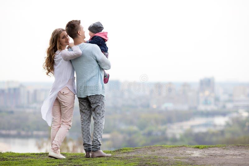 Gelukkige jonge familie op de stadsachtergrond royalty-vrije stock afbeelding