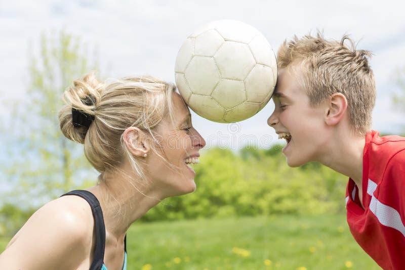 Gelukkige jonge familie speelvoetbal openlucht op een de zomerdag stock afbeeldingen