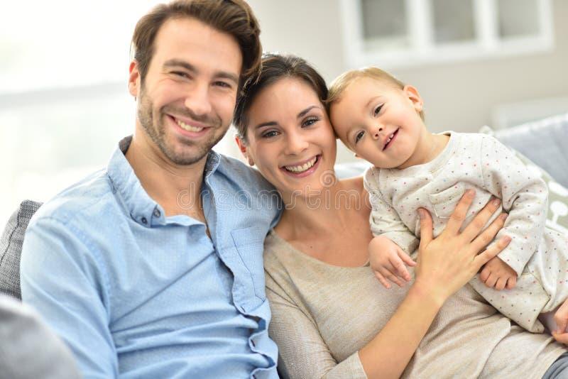 Gelukkige jonge familie van drie die samen op bank spelen stock foto's