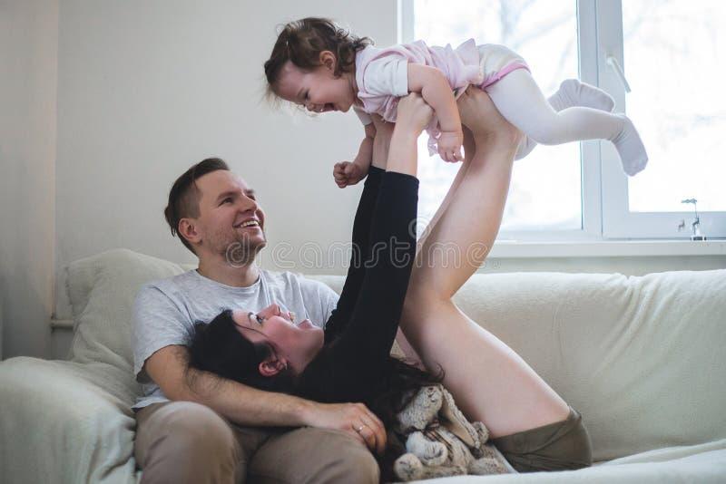 Gelukkige jonge familie van spel drie met dochter royalty-vrije stock afbeelding