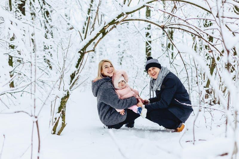 gelukkige jonge familiegangen met baby op de winterstraat, mamma, papa, c royalty-vrije stock foto