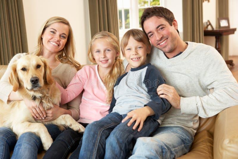 Gelukkige jonge familiezitting die op bank een hond houdt royalty-vrije stock afbeeldingen
