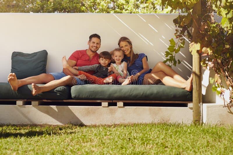 Gelukkige jonge familiezitting op terras stock afbeeldingen