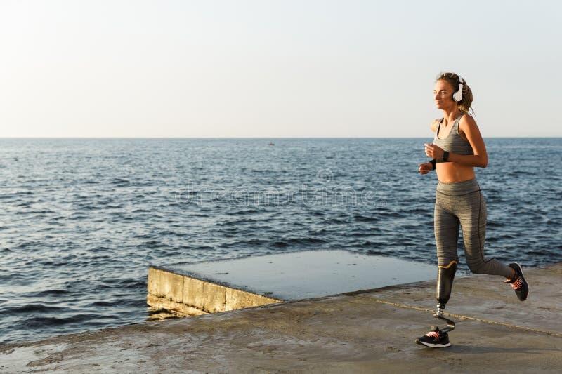 Gelukkige jonge gehandicapte vrouw met het prothetische been lopen stock foto