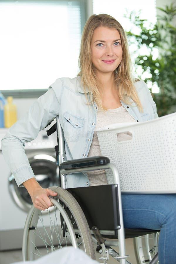 Gelukkige jonge gehandicapte vrouw in rolstoel die wasserij doen royalty-vrije stock afbeelding