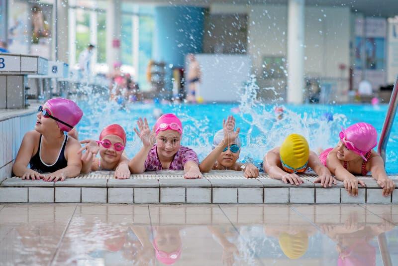Gelukkige jonge geitjes bij het zwembad De jonge en succesvolle zwemmers stellen royalty-vrije stock foto's