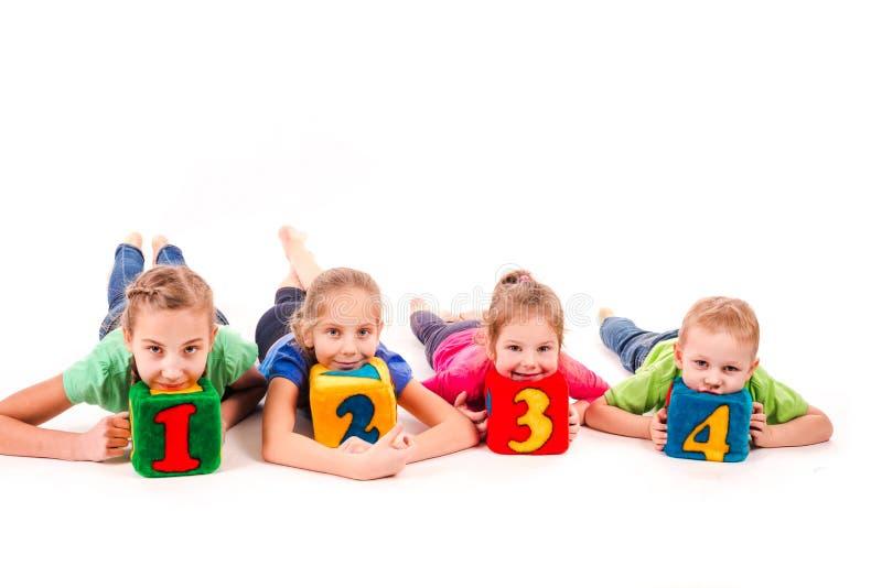 Gelukkige jonge geitjes die blokken met aantallen over witte achtergrond houden stock afbeelding