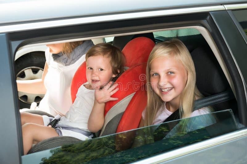 Gelukkige jonge geitjes die door auto reizen stock afbeelding