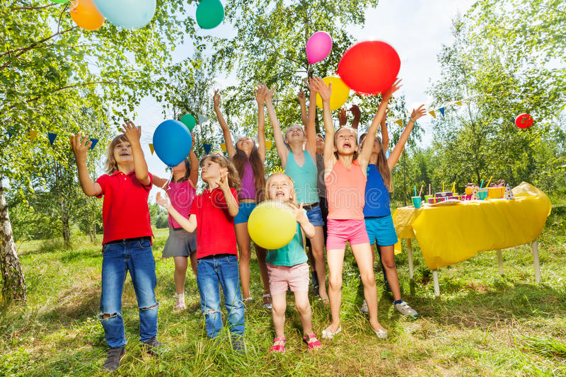 Gelukkige jonge geitjes die kleurrijke ballons buiten spelen stock afbeeldingen