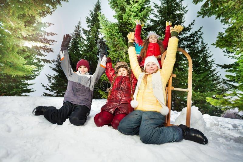 Gelukkige jonge geitjes die na de winterspelen rusten in sneeuwbank royalty-vrije stock foto