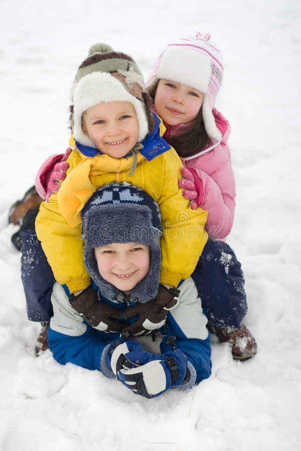 Gelukkige Jonge geitjes die in Verse Sneeuw spelen stock foto