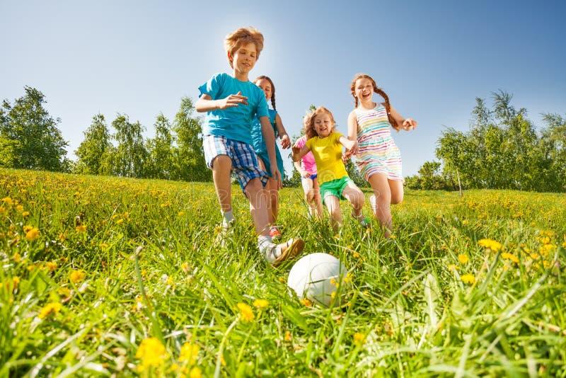 Gelukkige jonge geitjes die voetbal op groen gebied spelen royalty-vrije stock afbeeldingen