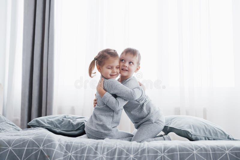 Gelukkige jonge geitjes die in witte slaapkamer spelen Weinig jongen en meisje, broer en de zuster spelen op het bed die pyjama's stock foto's