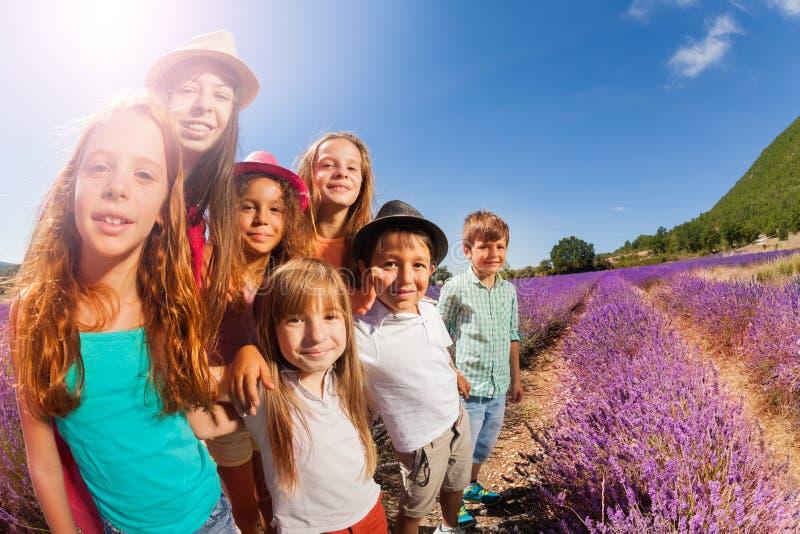 Gelukkige jonge geitjes die zich op lavendelgebied bij zonnige dag bevinden stock foto