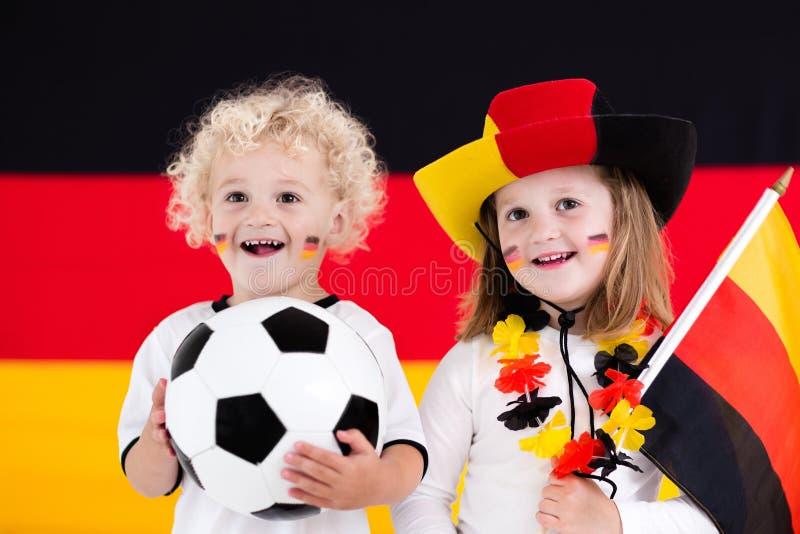 Gelukkige jonge geitjes, Duitse voetbalverdedigers stock afbeelding