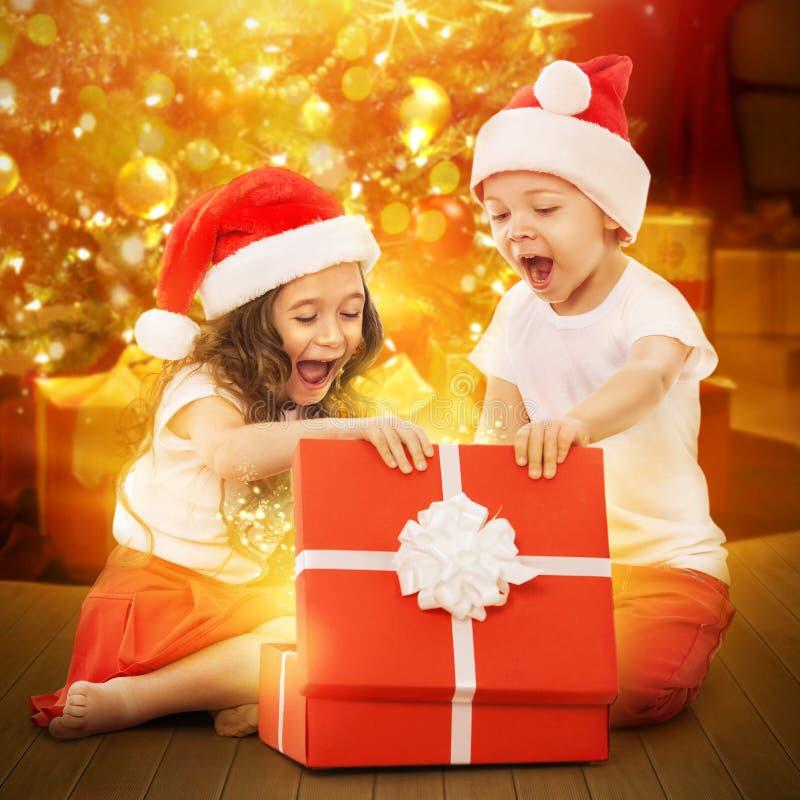 Gelukkige jonge geitjes in Kerstmanhoed die een giftdoos openen royalty-vrije stock foto's
