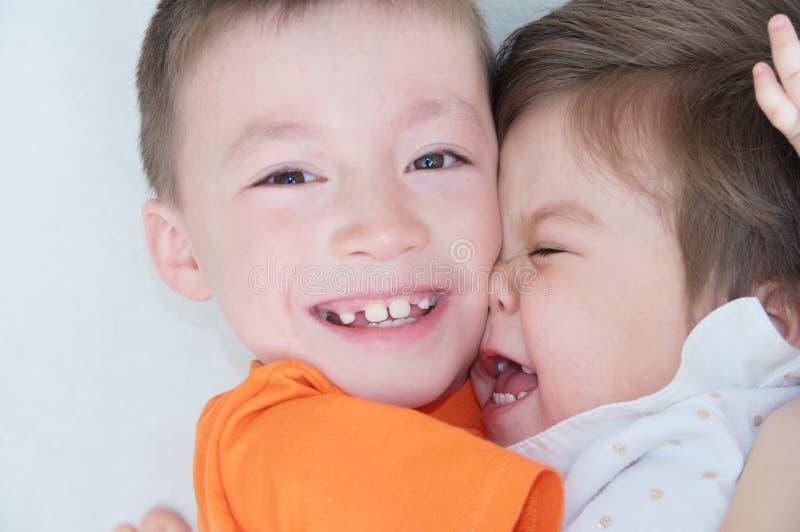 Gelukkige jonge geitjes, lachende kinderen die elkaar, close-upportret van jongen en meisje koesteren stock afbeeldingen