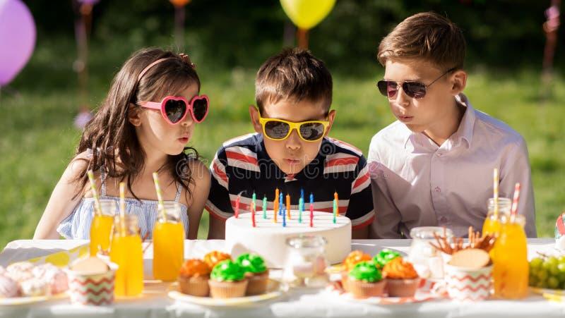 Gelukkige jonge geitjes met cake op verjaardagspartij bij de zomer royalty-vrije stock afbeelding