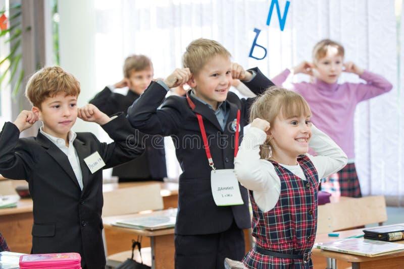 Gelukkige jonge geitjes in schoolklasse De kinderen hebben het doen van oefeningen Lage school royalty-vrije stock fotografie