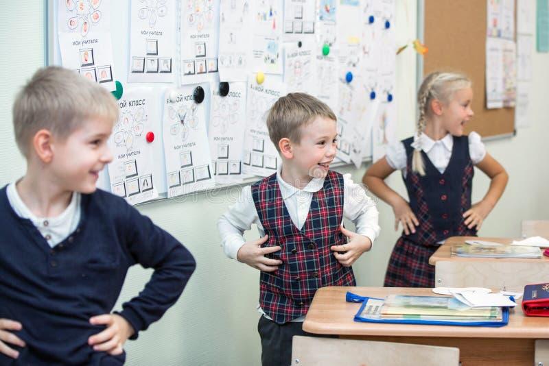 Gelukkige jonge geitjes in schoolklasse De kinderen hebben het doen van oefeningen Lage school royalty-vrije stock foto