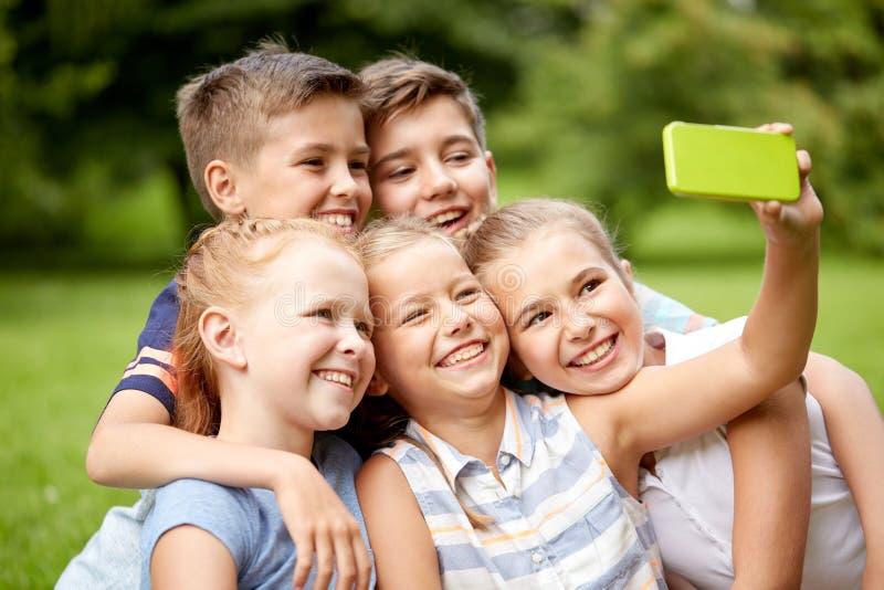 Gelukkige jonge geitjes of vrienden die selfie in de zomerpark nemen royalty-vrije stock fotografie