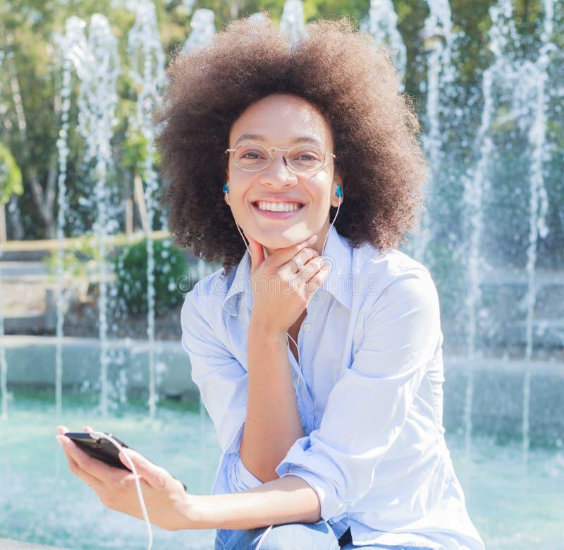 Gelukkige Jonge Gemengde Rasvrouw met Oortelefoons die Telefoon met behulp van royalty-vrije stock afbeeldingen