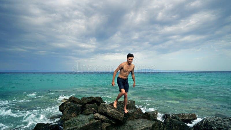 Gelukkige jonge geschikte tiener die op rotsen lopen die van vakantie genieten stock afbeelding
