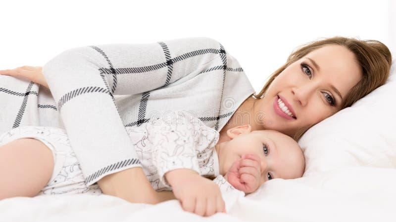 Gelukkige jonge glimlachende moeder en haar babyzoon die op een bed samen liggen Moeder en pasgeboren kindportret stock foto