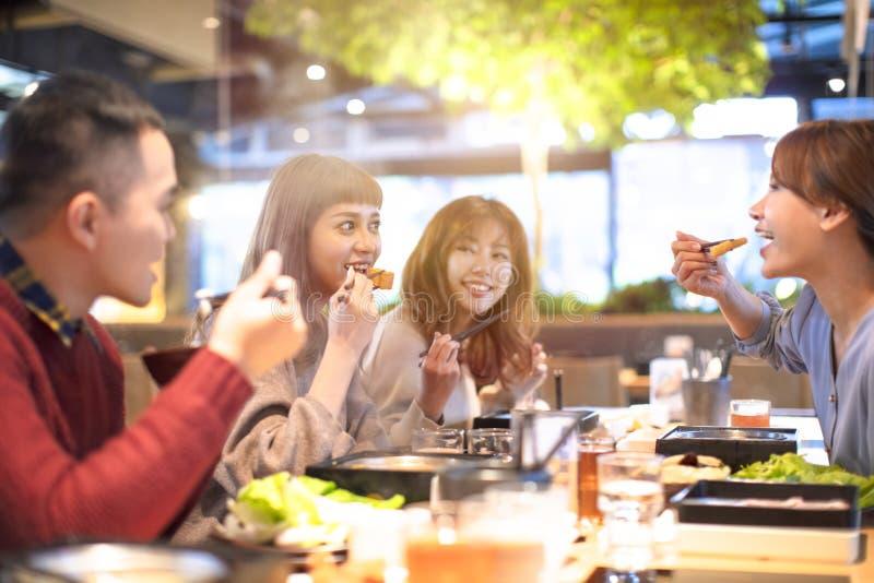 Gelukkige jonge Groep die in het restaurant eten stock fotografie