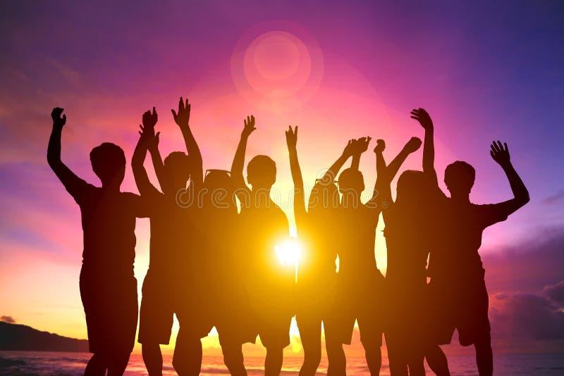 Gelukkige jonge groep die op het strand dansen royalty-vrije stock foto