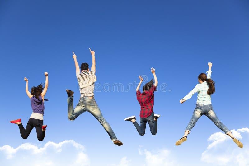 Gelukkige jonge groep die samen springen stock foto's