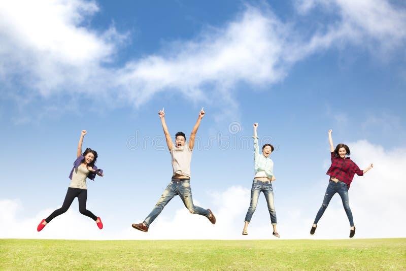 Gelukkige jonge groep die samen springen stock fotografie