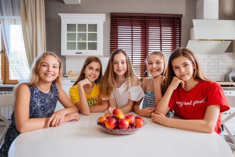 Gelukkige jonge groep vriendentieners die in de keuken zitten royalty-vrije stock afbeeldingen