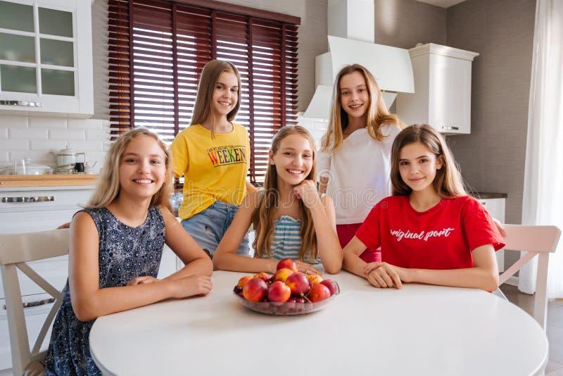 Gelukkige jonge groep vriendentieners die in de keuken zitten stock afbeeldingen