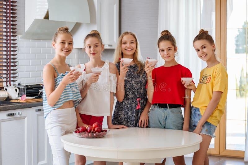 Gelukkige jonge groep vriendentieners die een fruit smoothies in de keuken drinken royalty-vrije stock fotografie