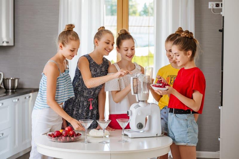 Gelukkige jonge groep vriendentieners die een fruit smoothies in de keuken koken royalty-vrije stock foto