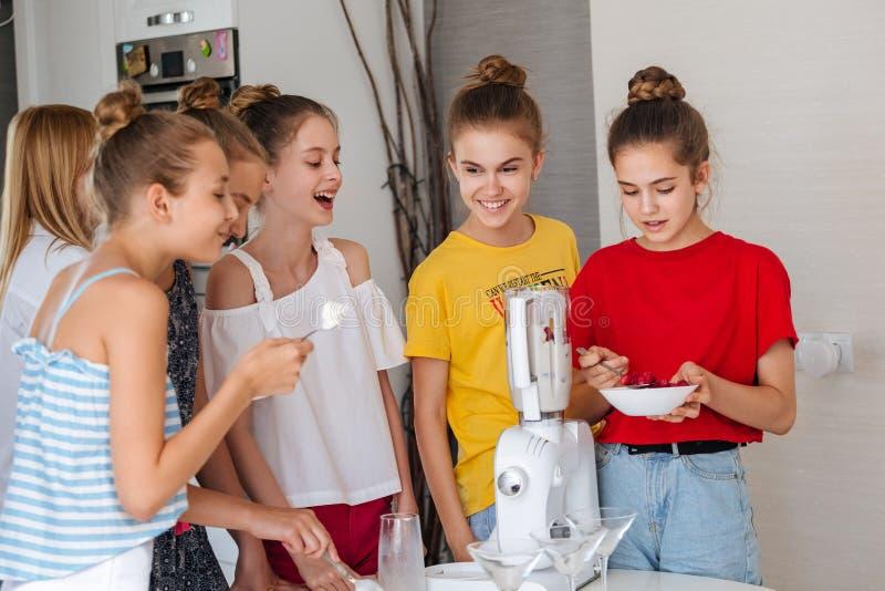 Gelukkige jonge groep vriendentieners die een fruit smoothies in de keuken koken royalty-vrije stock fotografie