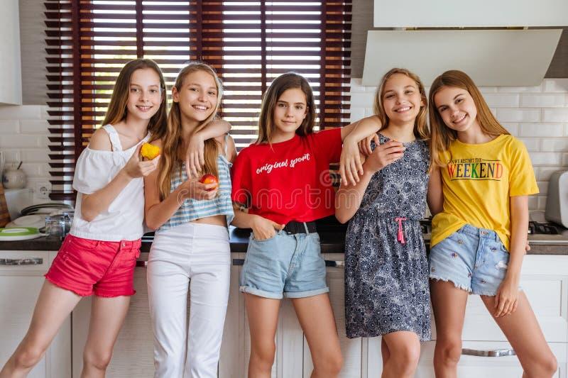 Gelukkige jonge groep vriendentieners eten vruchten in de keuken royalty-vrije stock foto's