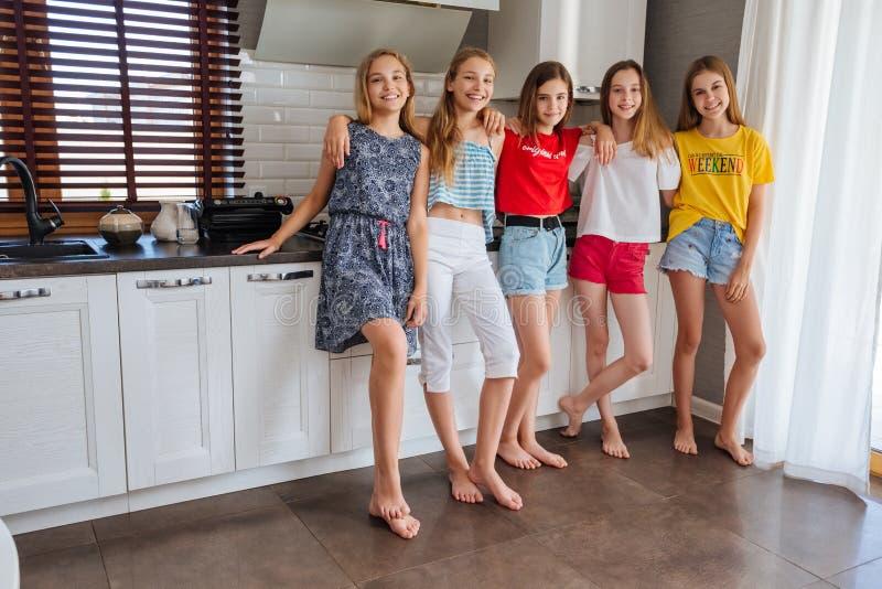 Gelukkige jonge groep vriendentieners eten vruchten in de keuken stock afbeeldingen