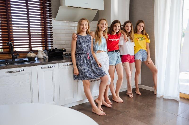 Gelukkige jonge groep vriendentieners eten vruchten in de keuken royalty-vrije stock foto