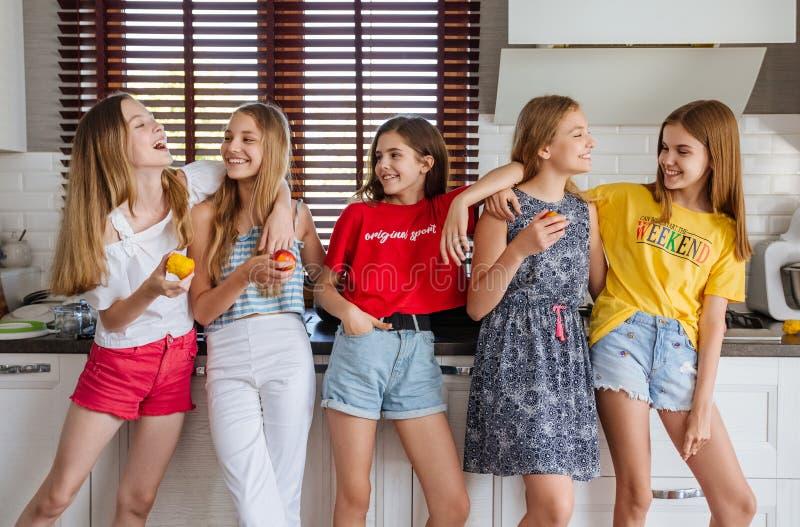Gelukkige jonge groep vriendentieners eten vruchten in de keuken royalty-vrije stock afbeeldingen