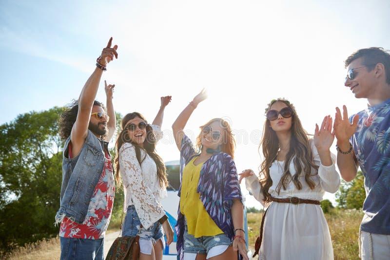 Gelukkige jonge hippievrienden die in openlucht dansen stock foto's