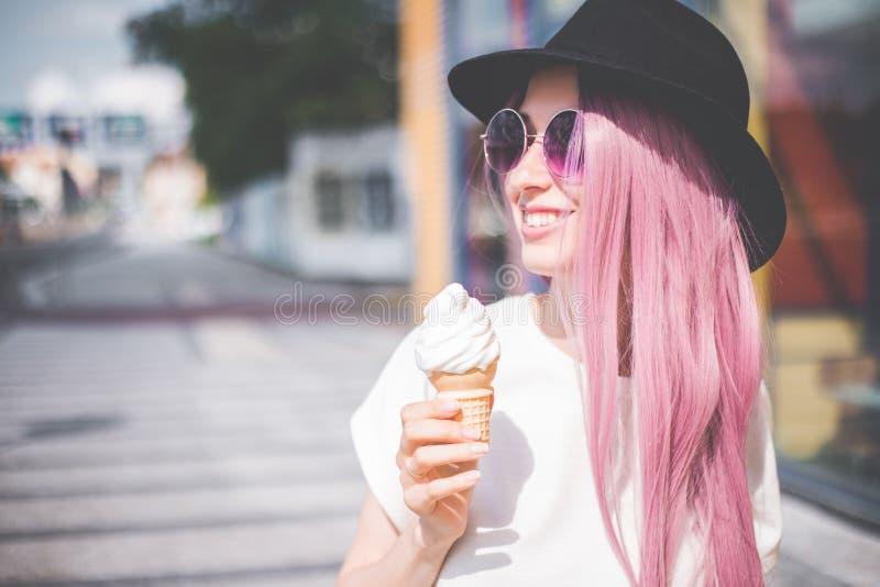 Gelukkige jonge hipstervrouw die met lange roze haar, hoed en zonnebril roomijs in openlucht eten royalty-vrije stock fotografie