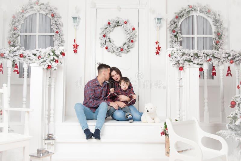Gelukkige jonge huiselijke manvrouw en kleine jongen op portiek van Kerstmis stock afbeeldingen