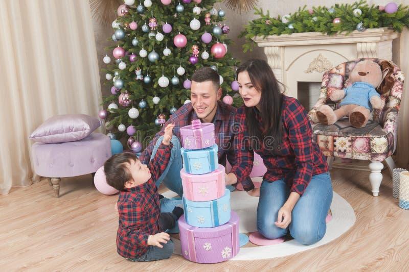 Gelukkige jonge huiselijke manvrouw en weinig Kerstmisgi van de jong geitjeholding stock foto