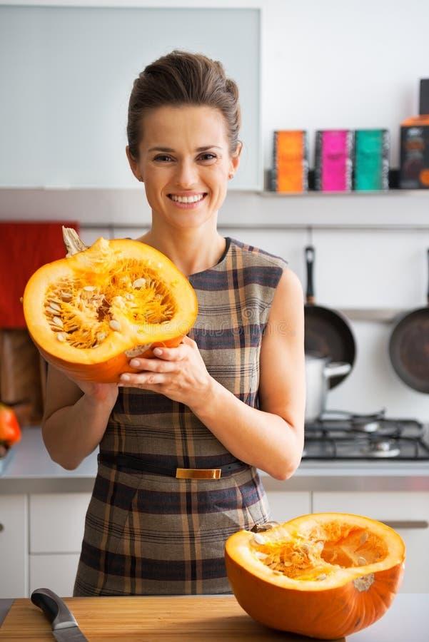 Gelukkige jonge huisvrouw die de helft van pompoen tonen stock afbeelding